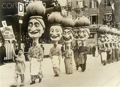 """Men W/Big-Head Costumes In Parade Nice, France- Fantastic floats again feature the annual and picturesque festival at the """"Playground of Europe""""--the 53rd annual Nice Carnival. Here are some of the """"Big Heads"""" in the procession that attracts thousands. Undated photograph circa 1925."""