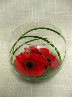 Red gerbera daisies inside a clear glass bowl lined with a few blades of lily grass create an inexpensive wedding centerpiece with lots of impact.