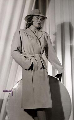 Visning på NK:s Franska, Nordiska Kompaniet mars 1943. En kvinnlig modell poserar iklädd kappa och hatt. Foto: Erik Holmén, 1943. CC-BY.