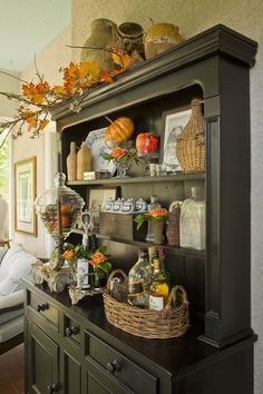 For this fall decor, entrepreneur and store owner Mary Carol filled a tall apothecary jar with faux pumpkins and tucked artificial tree twigs into an existing display.