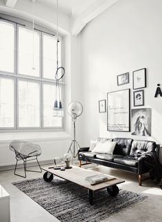 Living room - Black leather couch, textured rug, & frame wall.