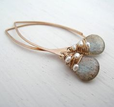 Slender hammered hoops with a stunning pair of Labradorite briollettes woven with three delicate fresh water pearls on each earring.Avaible in Sterling Silver or 14ct Rolled Gold*Beautiful light catcher. Simple lines, equally perfect for everyday or an occassion. A stunning gift beautifully packaged to be worn again and again. This is a very high grade of natural labradorite, it has a deep grey translucent hue, and flashes of blue and umber as the light shines through it - magical. Sarah…
