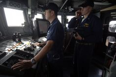 Hospital Corpsman 1st class Roy Pinedo stands the conning watch as officer of the deck as Lt. j.g. Chris Wolff communicates with coastal patrol craft USS Chinook (PC 9) in the waters off Iraq.