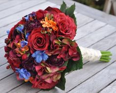 Fall flower wedding bouquet with the added touch of blue delphinium, stems wrapped in antique ivory ribbon adorned with pearl pins down the side. See more here: https://www.etsy.com/listing/204877642/vibrant-fall-wedding-bouquet-bridal?ref=shop_home_active_22
