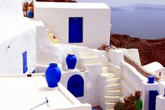 White house with blue doors and windows, and blue terracotta jars overlooking the sea. Oia, Santorini island, Southern Cyclades, Greece