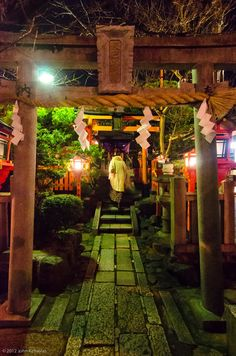 The Tatsumi Shrine in Kyoto, Japan, with a woman wishing perhaps for good fortune this night.