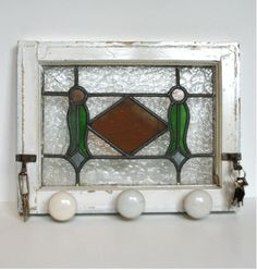 Hallway/front door organizer made from old stain glass window, hooks and door knobs.