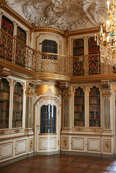White and gold ornate library with decorated ceiling, iron-work balcony, crystal chandelier, and glass-covered shelves. (I don't know if you're allowed to read a beat-up paperback in this room.) Christiansborg Castle, Copenhagen, Danemark. Photo by Talbot Merlotti via Flickr