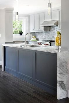 Two modern light pendants hang over a dark blue wainscoted kitchen island topped with a gray and white marble waterfall countertop fitted with a sink and gooseneck faucet.