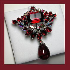 "Exquisite rare siam red drop brooch and earrings Signed SHERMAN  The stunning brooch and beautiful clip earrings are fashioned with brilliant red Swarovski crystals. The brooch, measuring 2 x 2 1/2"" comes with clip earrings to match measuring about 1"" in length. See more under SHERMAN JEWELRY on www.letsgetvintage.com"