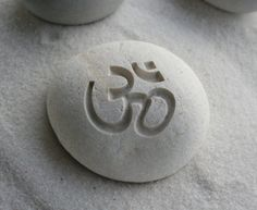 """Om is reputed to be the resonant vibrational tone of the non-dualistic universe as a whole. In Buddhism, Om corresponds to the crown chakra and white light.  This sacred symbol is deeply carved on a 2 1/2"""" beach pebble."""