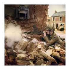 """Private W. Wheatley of 'A' Company, 6th Battalion Durham Light Infantry, 50th (Northumbrian) Infantry Division, fires his Bren gun from a ruined house in Douet, near Bayeux, 11 June 1944."" (Imperial War Museum caption)"