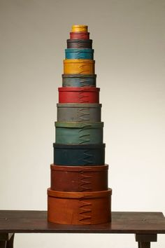 A graduated stack of 12 Shaker boxes in colorful,original painted finishes with three to five swallowtails patiently assembled & upgraded ov...