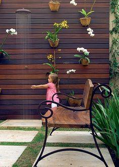 A pequena Sophia sempre deixa a sua brinquedoteca para curtir o jardim. Ao fundo, as orquídeas dão cor ao painel vertical de madeira, que recebeu um chuveirão para refrescar as crianças nos dias de calor. Projeto da paisagista Irene Cisneros. Foto: Revista Casa e Jardim