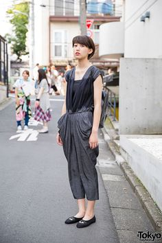 18-year-old Emika on the street in Harajuku wearing a resale dyed jumpsuit with a leather backpack and flats.