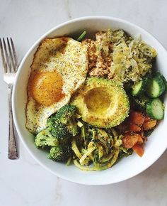 We've got a powerhouse bowl in our midst today! #WildPlanet salmon, greens, zoodles, broccoli, cucumber, tomato, kraut, fried egg, avocado and seasoning from @naturalistamaven.