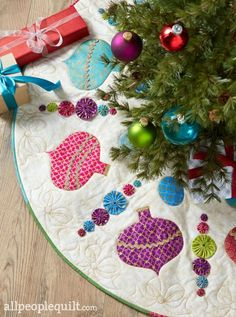 Shiny Baubles- Designer: Sharon Wasteney Fusible ornament appliqués and metallic embellishments combine in a merry and bright tree skirt. #shinybaubles #quiltsandmore #ornaments #winter #holidays #quilting #treeskirt