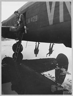Original wartime caption: Picture (issued 1944) shows - A curious study in reflections. Two of the ground crew of a Lancaster II stand at its rain-soaked dispersal point. Lancaster Bomber, Maximum Effort, Horsham, Airplanes, Caption, Ww2, World War, Photographers, Rain