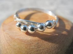 Whether you choose to wear this ring everyday or on special occasions, you'll love the simplistic beauty it brings to you wardrobe!  The sterling silver beads flow along a curve, adding movement to the design.  One bead measures 3cm. $20.00