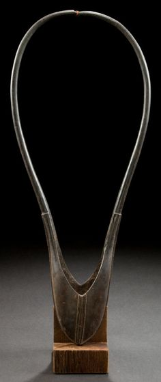 A KENYAN CARVED HORN ERRAP  Massai, early 20th century  22 inches long (55.9 cm)    The arm band of carved horn and copper wire worn by a warrior who has killed a man in battle.