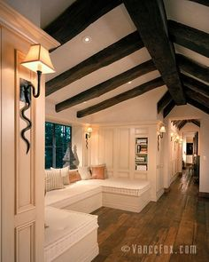 Very elegant and unusual foyer. Beams are big and bold against the white backdrop, and the handscraped hardwood floors look great in this space