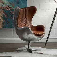 This modern rendition of the mid-century classic is perfectly crafted and luxurious. Entirely bold and timeless.The Aviator Egg Chair features upholstery in vintage full grain leather, wrapped in riveted polished aluminium panels replicating the famed Spitfire design, with a tilt and swivel steel ba