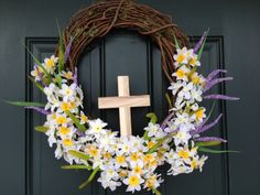 Easter Wreath:  My Easter Wreath is on the door.......and we are preparing for possibly 6 inches of snow....just doesn't seem right :)  My inspiration for this wreath was from another pinner.  She has an indoor wreath with a much longer more narrow cross and less flowers.  Thanks for the inspiration fellow pinners. The hardest part was finding a plain cross at the craft stores.  Wishing I was closer to Hobby Lobby.  I'm sure they would have them.