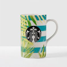 A+slender+ceramic+coffee+mug+with+blue+stripes+and+palm+frond+art.