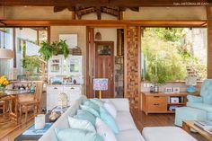 Casa com arquitetura rústica em Ilhabela tem muito vidro e móveis de madeira.