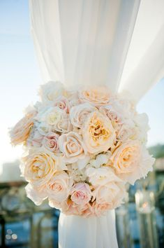 All white wedding ceremony with flowers in whites and nude colors, using Sahara roses, white ranunculus, white roses ... Love the flowers holding up curtains