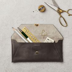 Luxury leather pencil pouch featuring a brass stud fastening and debossed logo. Golden Birthday, Pencil Pouch, Swatch, Stationery, Product Launch, Brass, Wallet, Dark, Luxury