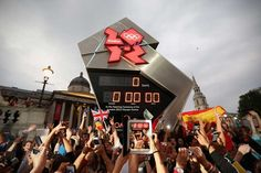 People celebrate the opening of the London 2012 Olympic Games at the Olympic countdown clock in Trafalgar Square.