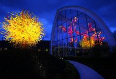 """""""The Sun,"""" left, and the """"Glasshouse"""" are shown during dusk at the new Dale Chihuly Garden and Glass museum at the Seattle Center. Photographed during a preview on Wednesday, May 16, 2012."""