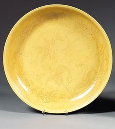 A yellow-glazed incised dish, China, Ming dynasty, Jiajing mark and period.