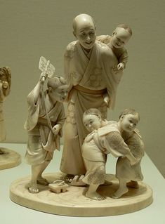 Figurine (Man carrying one child; three children at his feet.); Ivory, Japan, late 19th century, 16.5 x 10.8 x 9.5 cm. An okimono may be a small Japanese carving, similar to, but larger than netsuke. Unlike netsuke, which had a specific purpose, okimono were purely decorative and were displayed in the tokonoma.