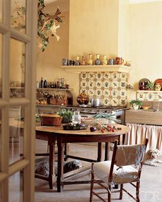 French Country Living -  In a 17th-century farmhouse in the South of France, A lively backsplashes using antique tiles from Southern Italy. With a Louis XIV farm table, a skirted farm sink, and plenty of open shelving, it's the kind of kitchen you want to spend all day in.