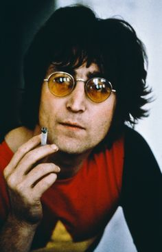 John Lennon wearing sunglasses and smoking.