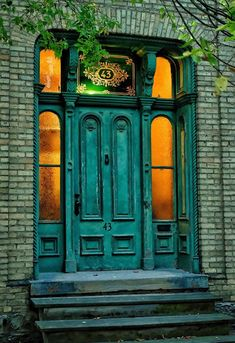 Victorian era aged turquoise door with sidelights. Looks like a London-build. Warm lighting inside on an early winter evening.