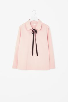 This shirt is made from a lightly textured blend of cotton and silk with a grosgrain ribbon tie fastening on the neckline. An A-line shape, it has a v-neckline, 7/8 sleeves and a wide rounded collar.