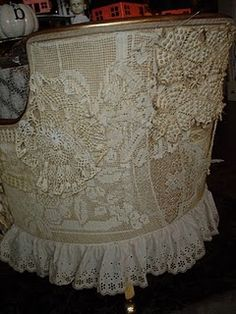 The use of tea stained antique crochet doilies and scarves to cover the entire back of the chair