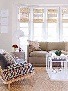 natural light filled living space with subdued palette | spindle arm wood chair + modern white coffee table + woven blinds