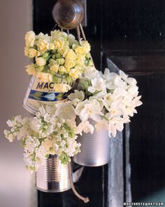 Hanging Tin Can Vases - See the one with the vintage label? That is cool....the others without the label just look cheap to me...the last thing I would want the guests at a wedding to be thinking about is what kind of soup or vegetables were in those cans before!!!
