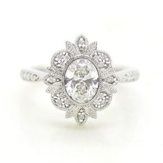oval centre diamond engagement ring with milgrain bead set halo detail