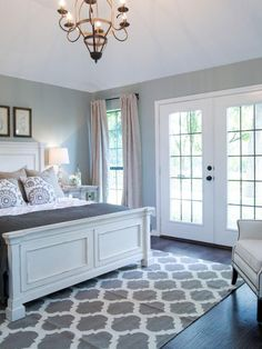 Bedroom decor ideas - traditional style with white, grey and blue color palette. Grey trellis pattern rug, french doors, traditional white wood bed, rustic chandelier.