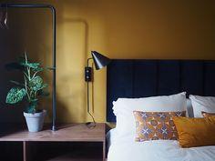 Mustard colour walls in the bedroom. Boho interiors. Yellow decor.