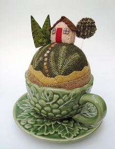 Aww! Regardless of cute landscape, a pincushion in a tiny teacup is a great idea! Glue the cup to the saucer, perhaps.