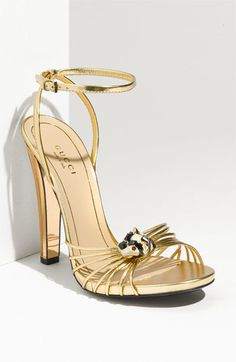 "Summer 2012 Gucci Ankle Strap Sandal in Gold Leather. ""A mirrored heel elevates a slim-strapped sandal adorned with a gilded tiger-head ornament.""  these hot-ass shoes are straight off of Michelle Pfeiffer in Scarface. seriously. if we don't see J-Lo in a pair of these this summer i will be seriously shocked. and appalled. these shoes MUST be worn.  not available til May 2012    4 1/2"" heel. $850"