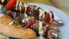 Lammekjøtt på spyd krydret med en spesiell kryddermiks og servert med tahinidip, tomater og rødløk.