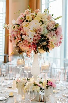 Tall and Dramatic Centerpiece atop white glass vase with hanging crystals surrounded by rhinestone stemmed candle holders