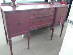 $350 - This elegant long legged buffet has two storage drawers and 2 cabinet doors for additional space. It has been painted a deep berry red with matching metal hardware. It measures 60 inches across the front, 19 inches deep. 38 inches to the tallest point. It can be seen in booth H 12 at Main Street Antique Mall 7260 East Main St ( E of Power Rd ) Mesa 85207  480 9241122open 7 days 10 till 530  Cash or charge 30 day layaway also available
